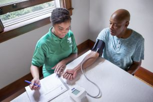 YMCA staff member taking a man's blood pressure and then recording the results