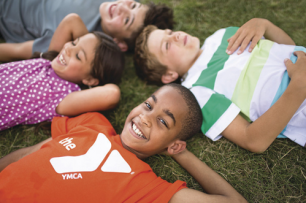 4 children laying down on the grass and smiling