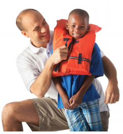 The adult puts on the life vest on the child