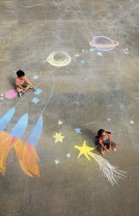 children on the ground drawing with a piece of chalk