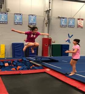 two girls- one jumps