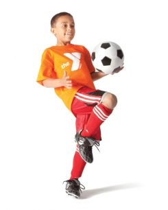 Boy wearing Y shirt bouncing soccer ball on knee