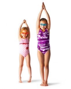 Two girls with swimsuits and swim goggles standing in diving poses